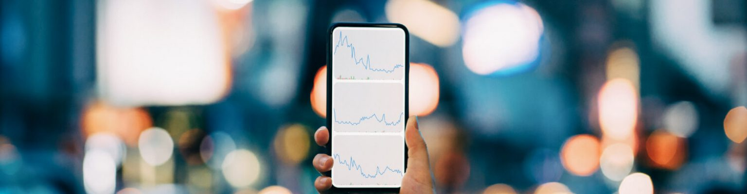 Woman's hand holding smartphone showing financial trading data with stock market crash sell-off against illuminated city street scene in downtown district at night
